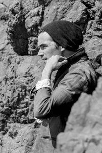 Black and white shot of Ian Harding, a man standing on a rocky wall, wearing a beanie and a grayish jacket