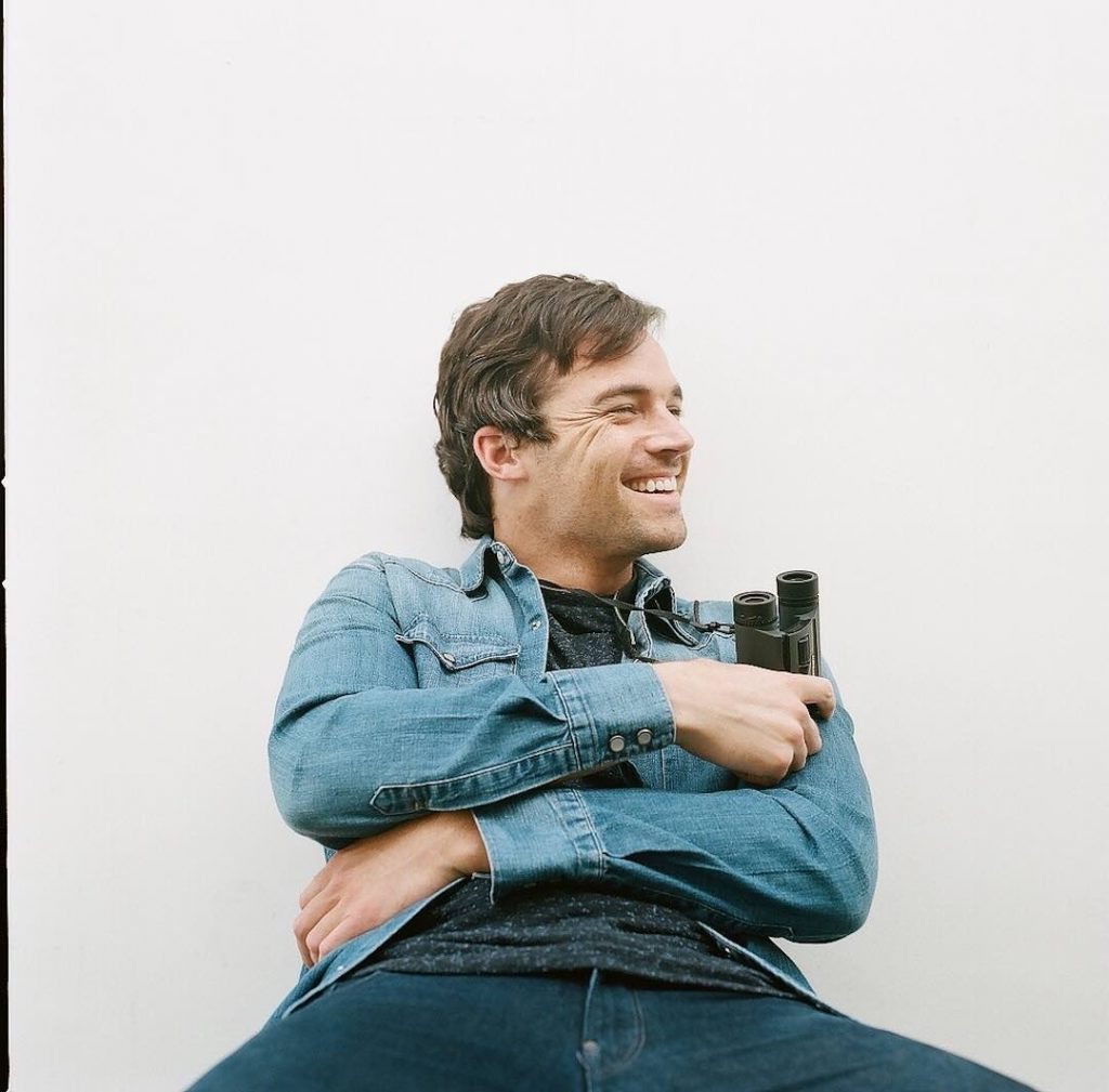 Ian Harding, a man with short brown hair sits leaned backwards against a white wall. He is looking to the side, smiling, holding a binoculars in one hand. He is wearing a blue jeans jacket and a black shirt and blue jeans.