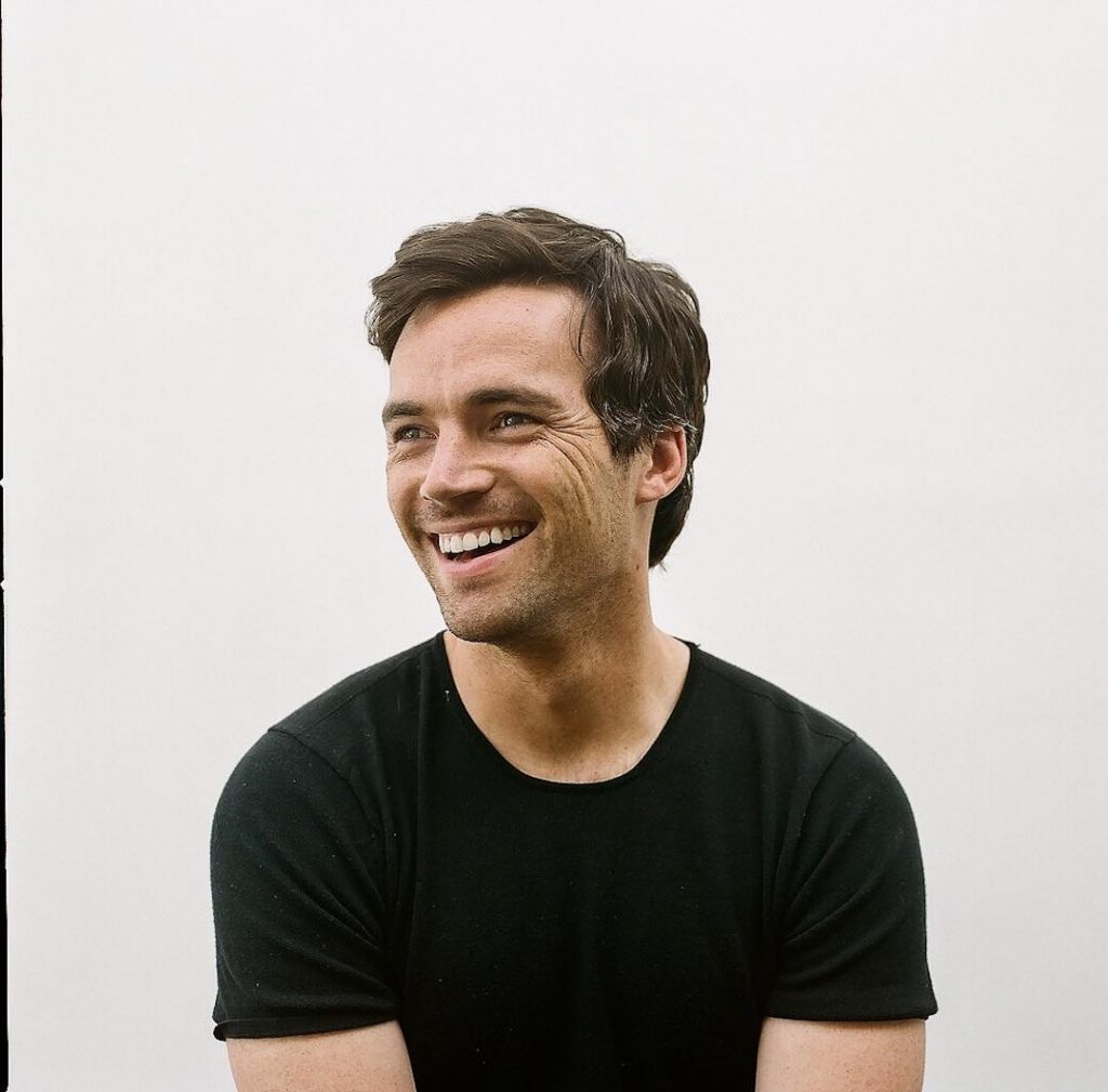 Ian Harding, a man with short, brown hair and a black shirt is sitting in front of a white wall. Ian is smiling with a slightly open mouth.