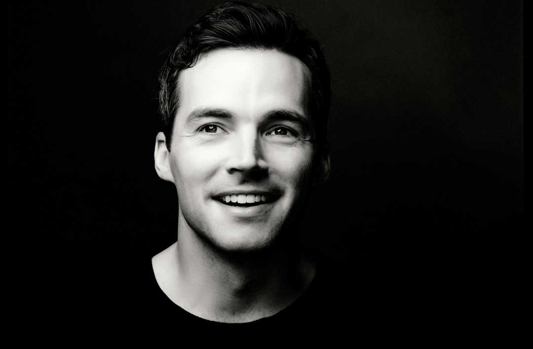 Black and white shot of Ian Harding, a man with short, brown hair and a black shirt. Ian is smiling with a slightly open mouth