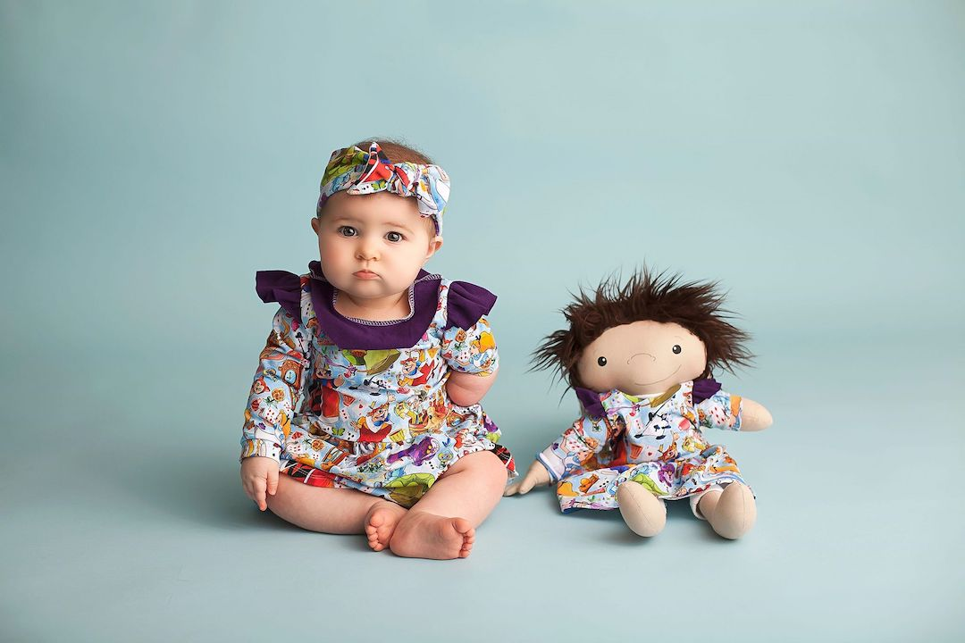A baby in a colorful outfit sits next to her doll with a limb difference