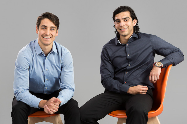 Team Evowalk: Two young men sitting on orange chairs, smiling.