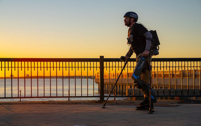A man walks across a bridge with an exoskeleton around his lower limbs during sunset