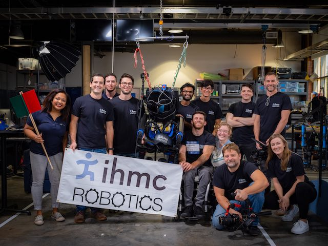 A group of people standing in a mechanics hall with a sign saying 'icmc robotics'