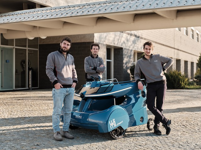 Three young men stand around a blue device used for ride-sharing for wheelchair users.