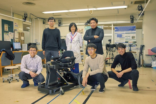 A group of people standing around a wheelchair they developed for the global mobility challenge.