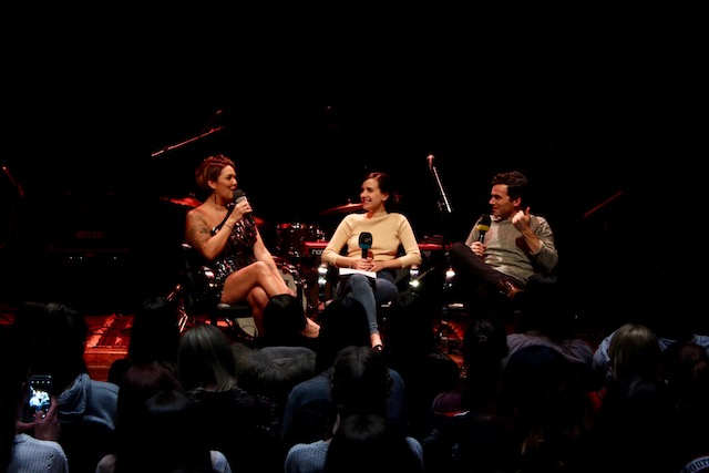 Three people sit on a stage. On the left side is a woman with curly brown hair and a black dress speaking into a microphone. In the middle is Susanne, a woman with brown hair, smiling to the left. And on the right side sits Ian Harding, a man with a grey shirt and brown hair.