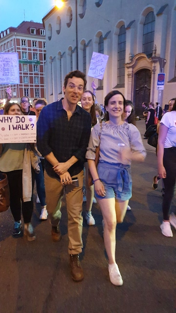 Ian Harding, a man wearing. black shirt and beige pants walks with Susanne, a woman with long brown hair, in front of a crowd of people holding up signs.