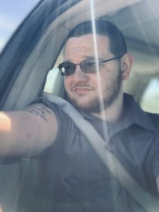 A man in a car looking out of the window. He is wearing a grey shirt, has a tattoo on his right arm and wears sunglasses