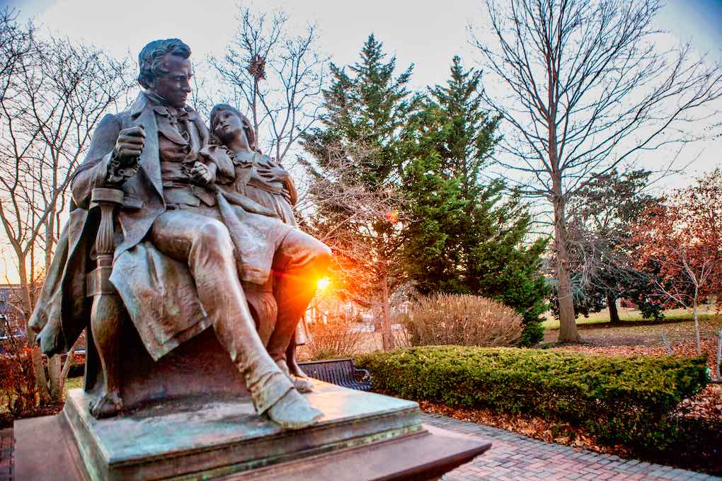 A statue at Gallaudet University in a park. A man with a small girl.