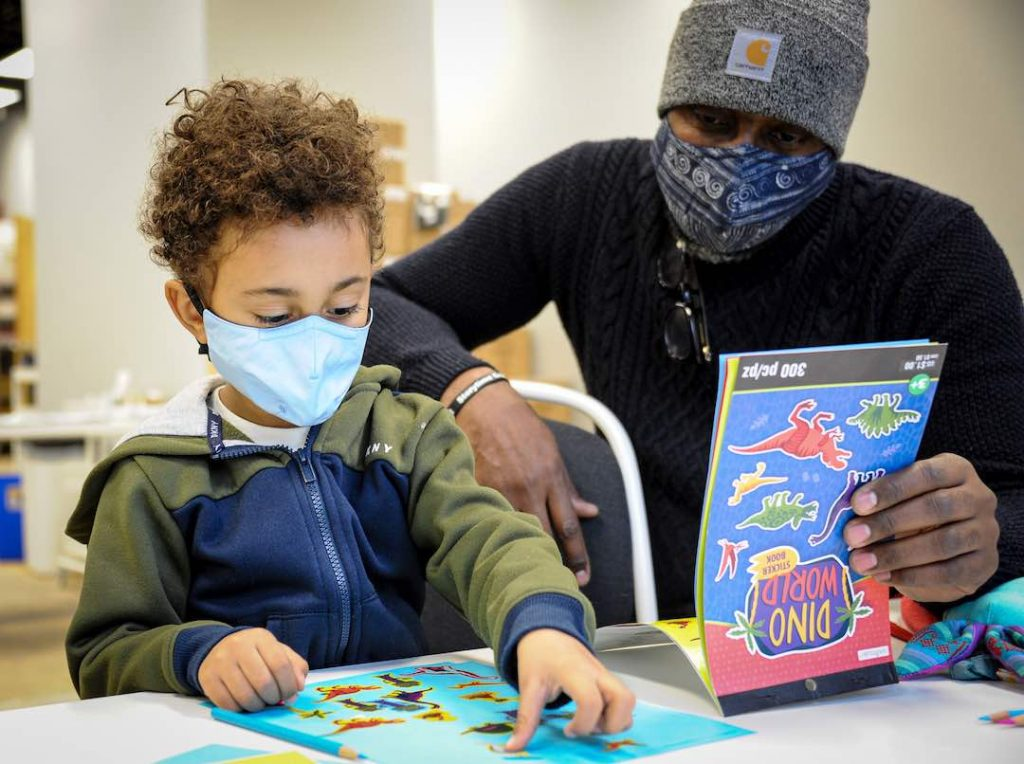 A little boy with curly brown hair and a blue face makes sits next to his dad who wears a warm hat and a blue face mask. The play a game together sitting on a table.