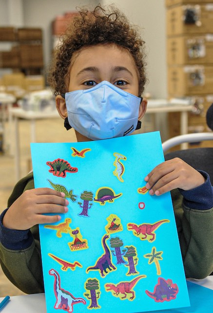 A boy with curly brown hair and a blue face mask proudly presents a paper with stickers of dinosaurs