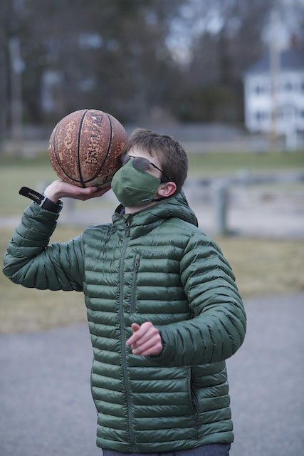 A boy with short brown hair and sunglasses wears a green face mask and throws a basket ball