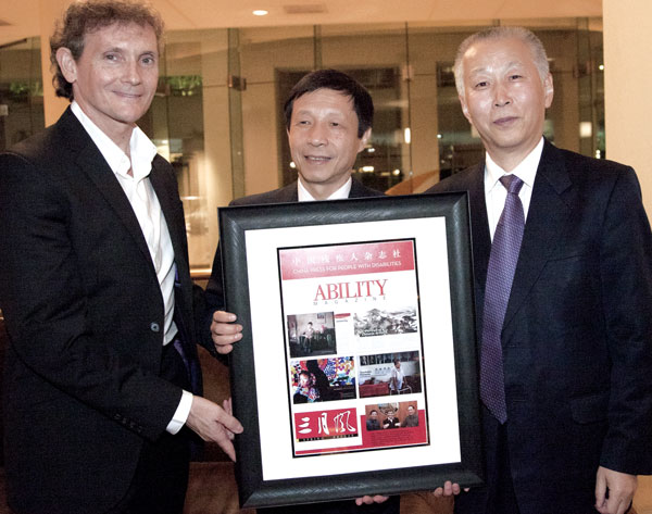 Chet Cooper, Ni Lin and Wei Mengxin holdig a framed award
