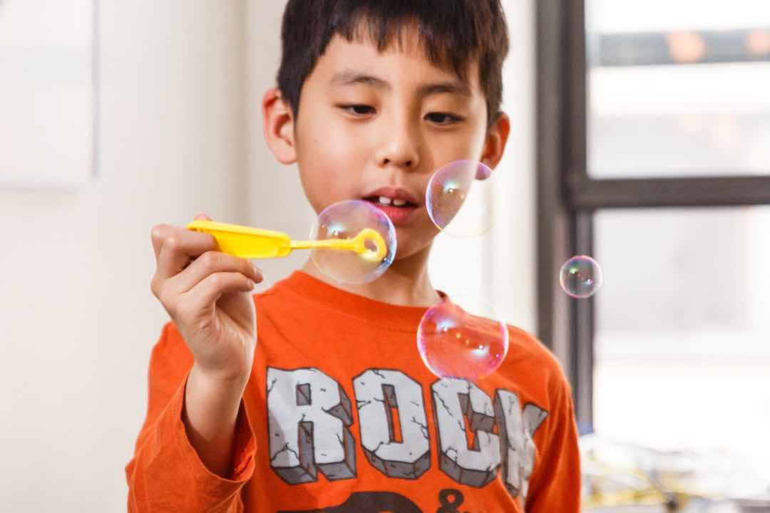 A young boy with brown hair and a red shirt that says 'Rock' is holding up a soap bubble device with four soap bubbles around him
